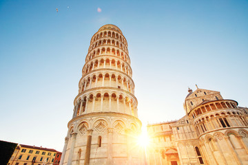 Pisa leaning tower and cathedral basilica at sunrise, Italy. Travel concept