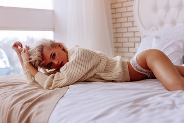 Young photo model wearing sweater and panties posing in bed