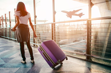 Young woman pulling suitcase in  airport terminal. Copy space Wall mural