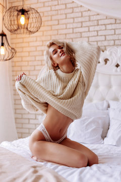 Blonde woman with bob cut wearing nice oversized beige sweater