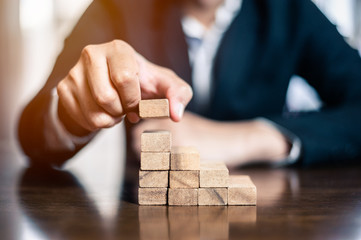 plan and strategy in business.risk concept.hand of man has piling up and stacking a wooden block.Businessman Building The Success. Fototapete