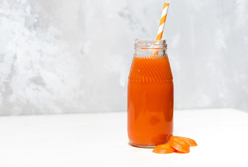 fresh carrot juice in a bottle on white background, closeup