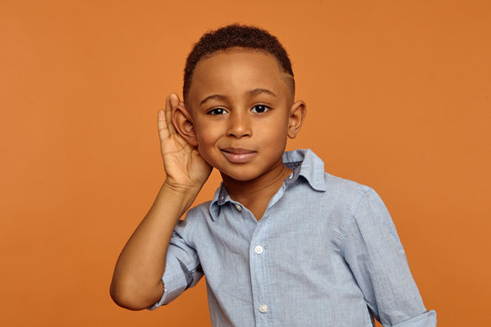 Overhear, spy and secrecy concept. Isolated studio portrait of cute nosy African ten year old boy spying on someone, keeping hand at his ear and listening attentively, trying to hear everything