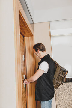 Man close door of home because he is going to work. Standing behind enter.
