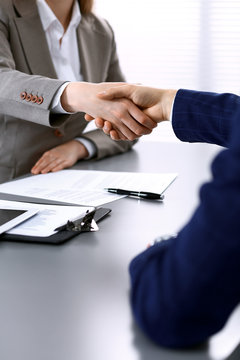 Business people shaking hands, finishing up a meeting. Papers signing, agreement and lawyer consulting concept