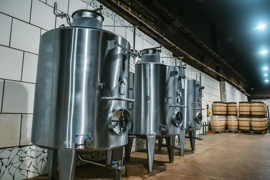 Stainless steel storage tanks or aluminium barrels or metal vats for wine production, industrial alcohol fermentation in vineyard cellar