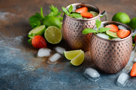 Moscow mule cocktail with ginger beer, vodka, lime, strawberries and mint in a cooper mugs.