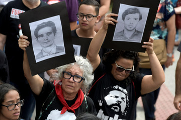 Demonstrators hold placards showing images of victims of dictatorship as they take part in a protest against celebrations marking the anniversary of a 1964 coup in Belo Horizonte