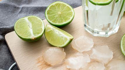 Fototapeta Limonka pokrojona na kawałki z kostkami lodu i szklanką do przygotowania napoju