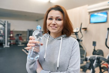 Portrait of smiling summer woman with bottle of water in gym. Health fitness sport age concept