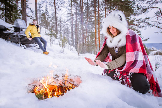 The girl is heated by the fire. Young people are resting in nature. Holidays in the mountains. rest in the winter. Bonfire on the snow. Traveling on a snowmobile. Snowmobile in the mountains.