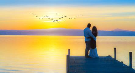 Wall Mural - escena romantica de dos enamorados mirando el atardecer en el lago