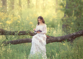 charming sweet girl with dark hair and bare shoulders in a gorgeous vintage white dress sits on a fallen tree and reads an interesting book of fairy tales, cute elf from the secret forest world