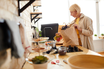 Content beautiful mature woman with short blond hair standing at kitchen counter and putting fruits in bowl while unpacking grocery bag