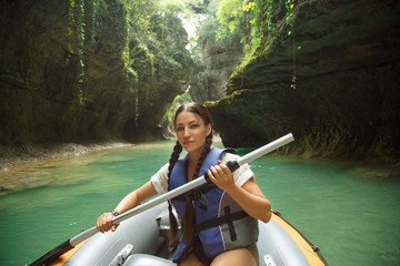 pretty young woman with dark hair gathered in two black braids, lady looks and poses for camera in life jacket and paddle in hands, tourist in inflatable boat sails through Martvili Kanyon in Georgia
