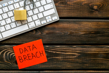 data breach concept with locker on keyboard on wooden background top view mock up