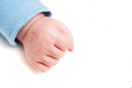 Close up of a child's fist on white background. Clenched fist - hand of child, baby power. New born baby hand