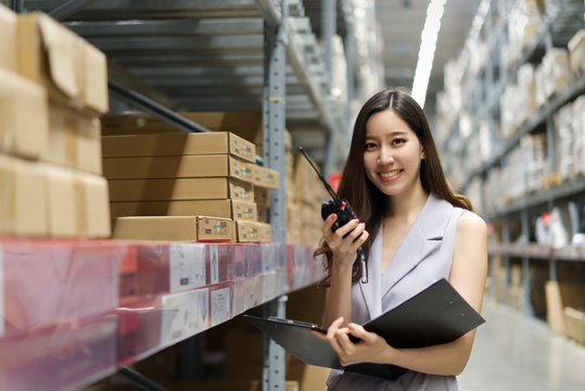 Smart smiling young Asian woman working in store warehouse. She is standing and holding document folder and radio communication equipment. She is feeling happy to work. Smart working girl concept.