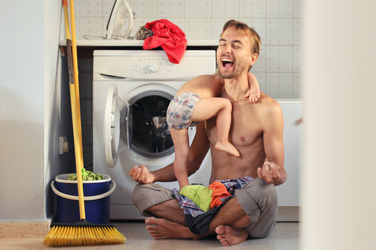 Young exhausted husband father sitting in lotus pose near washing machine with pile of clothes and child on his lap. He can not stay calm and screams. Housework, male housewife concept
