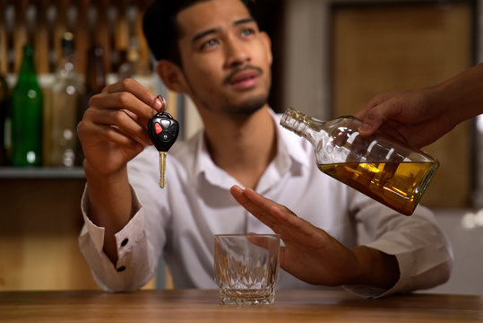Drink no drive, say no for safety, no more alcohol concept. The man sitting in restaurant holding the car key refusing alcohol from his friend to pour whiskey in his glass.