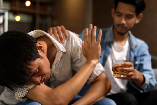 No more alcohol. Drunk man sitting on sofa refusing whiskey from his friend by raising his hand to stop while his friend try to cheer to drink it more in party night in restaurant.