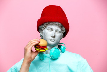 Antique bust of male in hat with hamburger