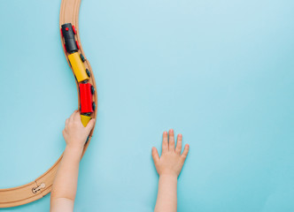 Kids hands playing with wooden toy train on blue background