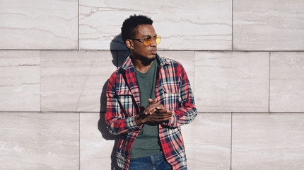 Wall Mural - Portrait stylish african man wearing red plaid shirt, looking away, guy posing on city street, gray brick wall background