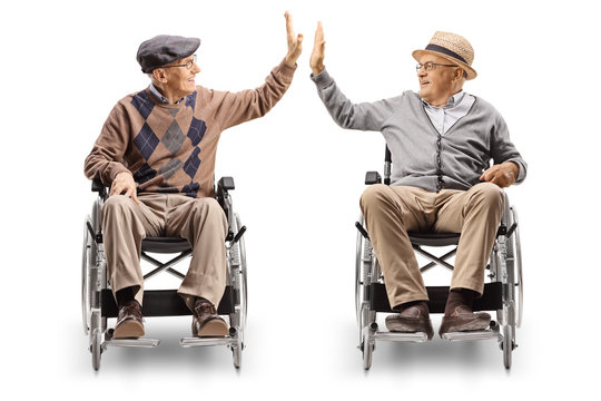 Two senior men in wheelchairs giving high-five