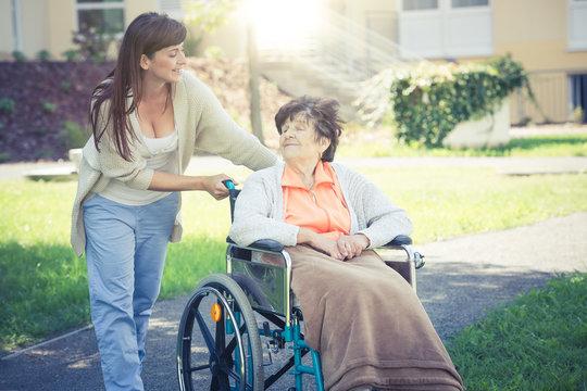 Seniorin im Rollstuhl mit Enkelin beim Spazierengehen
