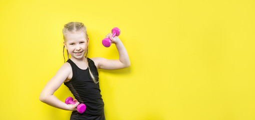 Theme sport and health. Beautiful caucasian child girl with pigtails posing on yellow background with smile. little athlete holding pink dumbbells. Banner for advertising, space for text copy space