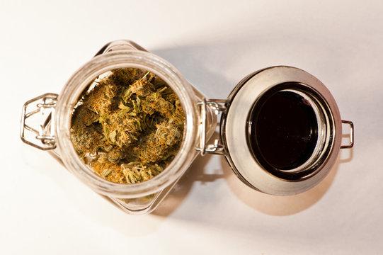 Marijuana buds in open mason jar on white background