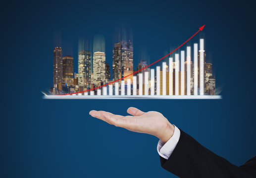 Real estate business investment concept. Businessman hand holding digital tablet with buildings hologram and increasing bar chart and graph
