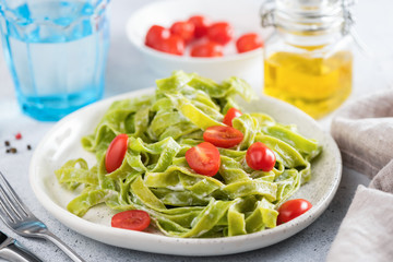 Green spinach pasta in creamy sauce with tomatoes on a plate. CLoseup view. Tasty pasta dinner