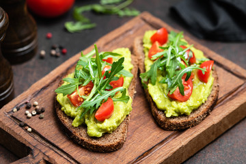 Vegan or Vegetarian Toast with mashed avocado, arugula served on wooden board
