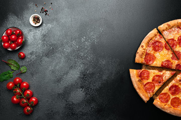 Pepperoni pizza on black slate background with copy space for text. Top view