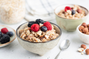 Healthy breakfast cereal porridge with berries and nuts in bowl. Closeup view.