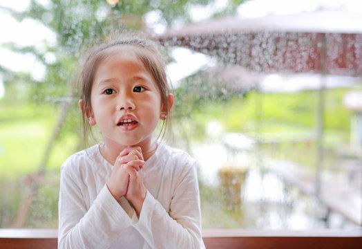 Happy little Asian kid girl praying at glass windows on the raining day.
