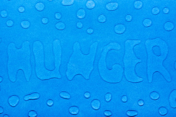 """The word """"hunger"""" is written with water droplets and water droplets on a blue smooth surface. Top view"""