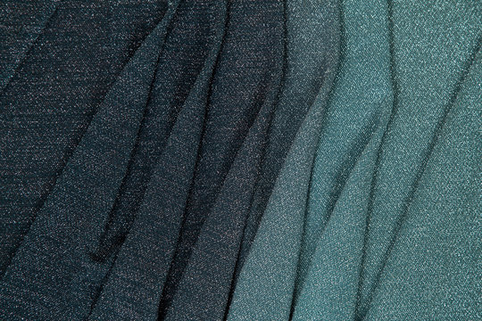 rainbow lurex fabric - the transition from light green to dark burgundy lined with different folds