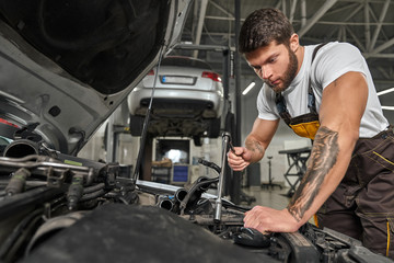 Strong man wearing coveralls repairing engine in automobile