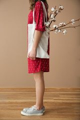 Young woman with cotton flowers in eco bag indoors