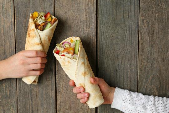 Female hands with tasty doner kebab on wooden background