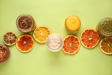 Jars of sugar scrubs with citrus slices on color background