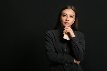 Stylish businesswoman with mobile phone on dark background