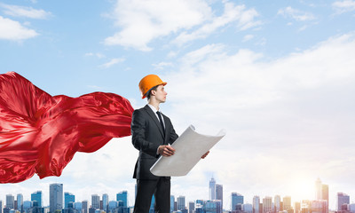 Concept of power and sucess with architect superhero in big city