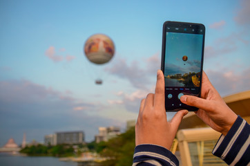A woman is taking a picture of a hot air balloon flying into the sky using a mobile phone