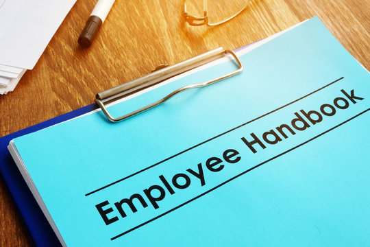 Employee handbook and clipboard on table.