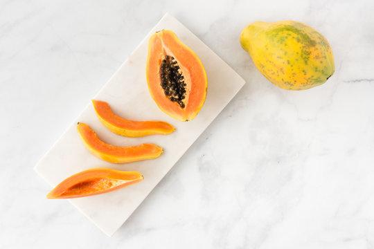 Whole, Half and Papaya Slices on White Marble