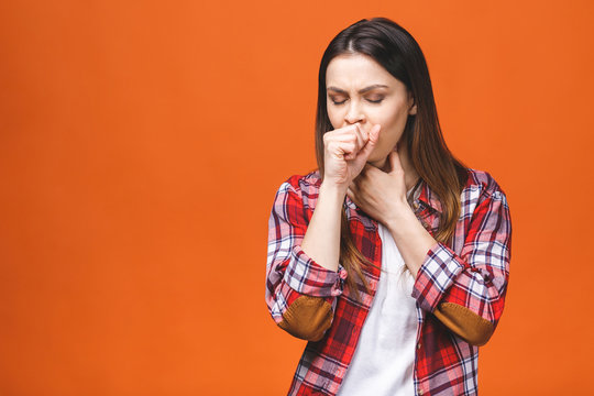 Attractive sick young brunette woman in checked shirt,  having sore throat, holding hand on her neck/ Throat pain, painful swallowing concept/ Inflammation of the upper respiratory tract